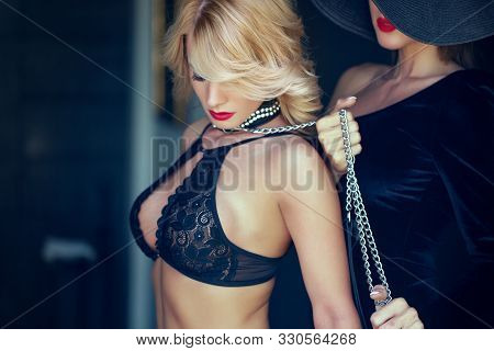 Sensual blonde shy woman in bra holded by lesbian lover on chain stock photo