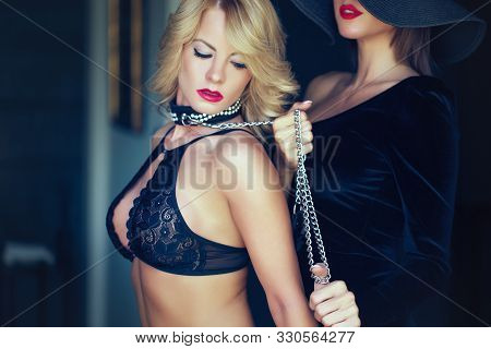 Sinful blonde woman in bra holded by lesbian lover on chain stock photo