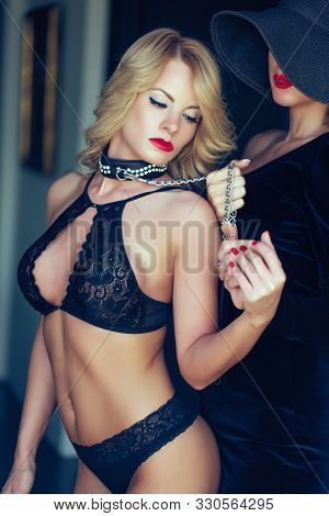 Sexy blonde woman in bra holded by lesbian lover on chain stock photo
