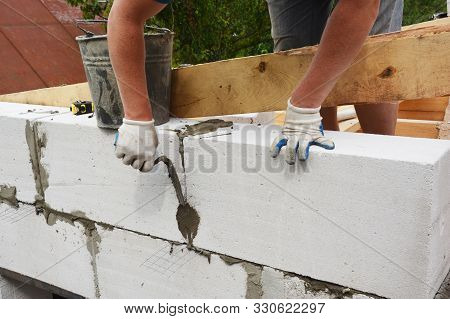 Bricklayer builder laying autoclaved aerated concrete blocks for house wall near unfinished roof wooden beams. stock photo
