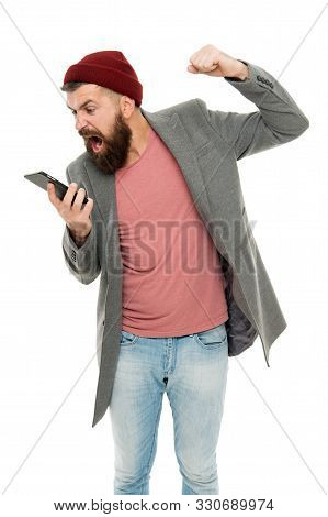 Making offensive blog comments. Angry hipster shaking fist at blog response in mobile device. Bearded man taking hard new blog post. Private blog making him angry. stock photo