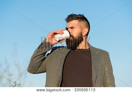 Time for myself. Hipster hold paper coffee cup. Relaxing coffee break. Drink it on the go. Man thoughtful bearded hipster prefer coffee take away. Businessman bearded guy drink coffee outdoors. stock photo