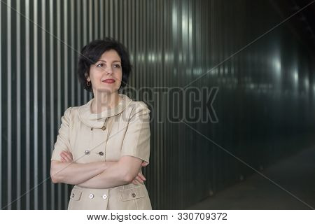 Portrait of smiling middle aged business woman with crossed arms on a warehouse striped wall with light reflections. Attractive middle aged woman with beautiful smile in business suit. stock photo