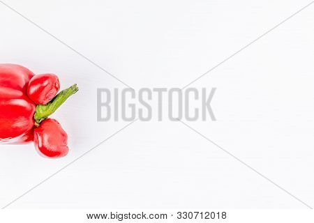 Trendy ugly organic farm vegetable - red sweet bell pepper with mutation parts on white background. Concept zero waste production in food industry and a world without starvation. Copy space. Top view. stock photo