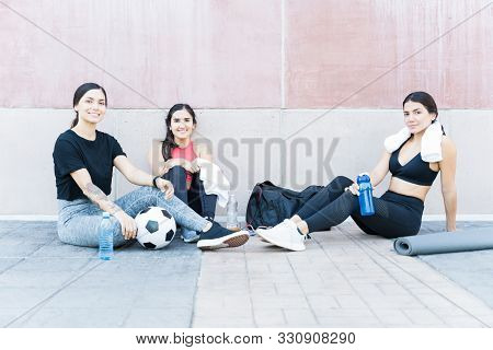 Portrait of attractive young active athletes sitting on footpath against wall stock photo