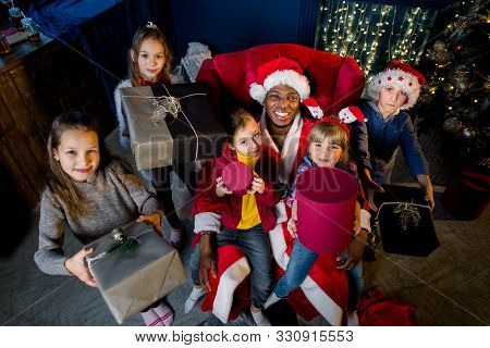 Beautiful children with gifts in their hands around African Santa sitting in an armchair on the background of a Christmas tree. stock photo