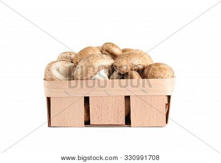 Fresh wild mushrooms in wood veneer basket on white background. Edible fungi stock photo