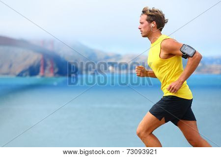 Athlete running man - male runner in San Francisco listening to music on smartphone. Sporty fit youn