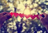 hands holding a string of paper hearts up to the sun amid sun conditioned with a retro vintage insta