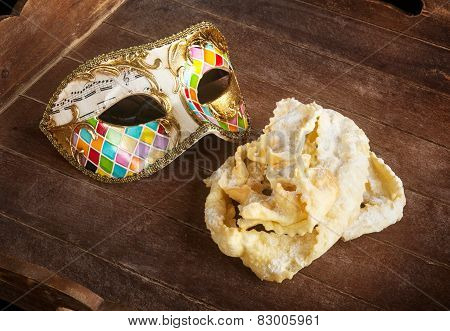 Typical fried pastry of italian carnival with venetian mask. These sweet are called in different ways chiacchiere Galani cenci or frappe. stock photo