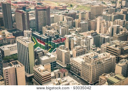 Close up detail of skyscrapers the business district of Johannesburg - Aerial view of modern buildings of the skyline in South Africa biggest city with southafrican flag painted on structure walls stock photo