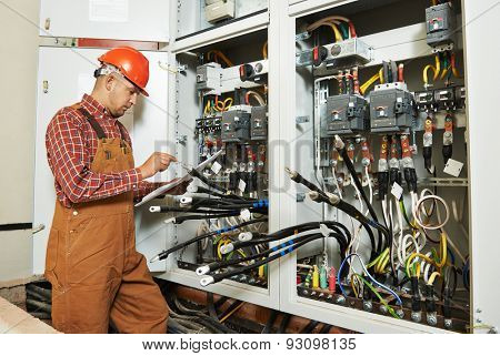 adult electrician builder engineer worker with electric scheme plan in front of fuse switch board stock photo