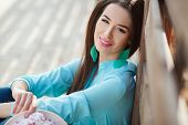 Attractive young lady sitting close to the wooden wall