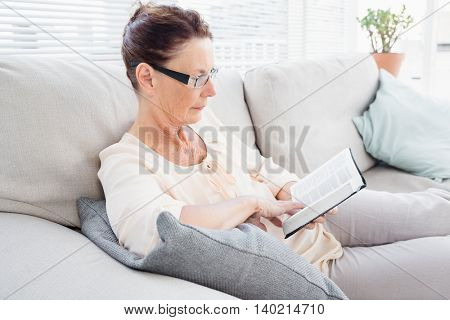 Concentrated mature woman reading book while resting on sofa at home stock photo