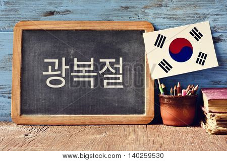 a chalkboard with the text National Liberation Day of Korea written in Korean and a flag of South Korea, on a rustic wooden surface, against a blue wooden background stock photo