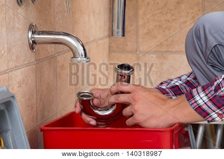 Close-up Of Plumber's Hand Fixing Sink In Bathroom stock photo