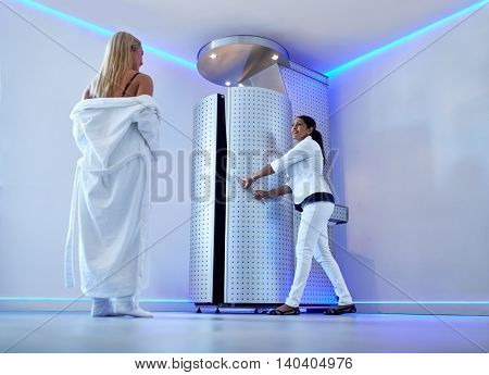 Full length portrait of woman in bathrobe at cosmetology clinic going for cryotherapy treatment in cryosauna. Nurse standing at the door of freezing capsule. stock photo