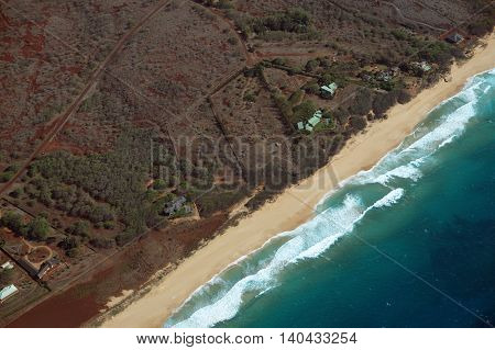 Aerial of Northwest coast of Molokai with waves crashing into long sandy beach and surrounding area of island with roads largely undeveloped. April 2016. stock photo