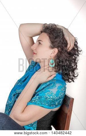Young model in her mid twenties wearing aqua colored earrings of middle eastern design and a blue shawl. stock photo