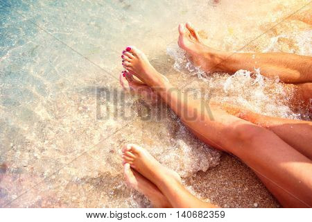 Summer holidays, Vacation concept. Family sitting on sandy beach in water. Bare feet.