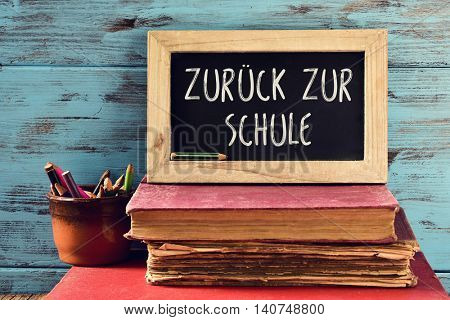 closeup a chalkboard with the text zuruck zur schule, back to school written in German, on a pile of old books and a pot with some pencils, against a rustic blue wooden background stock photo