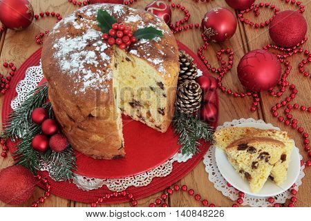 Traditional Italian panettone christmas cake and slice with holly berries, pine cones, red bauble decorations and bead strands over oak table background. stock photo