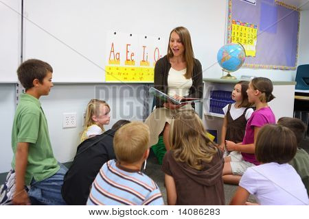 Elementary school teacher reads story to class stock photo