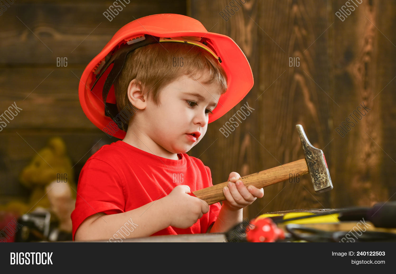 Kid Boy Hammering Nail Into Wooden Board. Child In Helmet Cute Playing As Builder Or Repairer, Repai