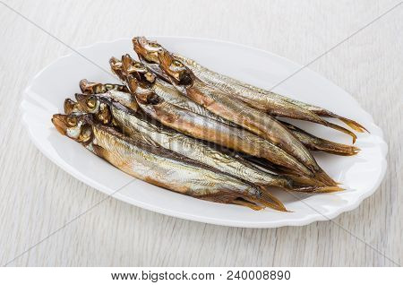 Heap of smoked capelin in oval dish on wooden table stock photo