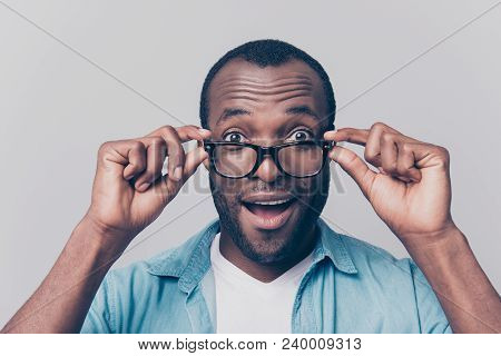 Omg! I can see you perfectly!  I have good vision! Close up portrait of excited cheerful glad satisfied surprised afro guy taking off his unnecessary glasses isolated on gray background stock photo