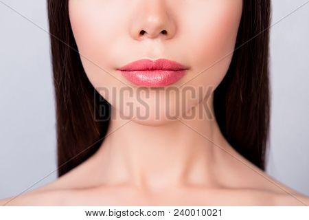 Plastic surgery concept. Lips filling, ideal and perfection mania. Cropped close up photo of young brunette woman`s lips on light background stock photo