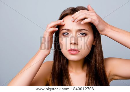 Close up portrait of frustrated sad upset beautiful young woman is squeezing out pimples on her forehead, isolated on grey background stock photo