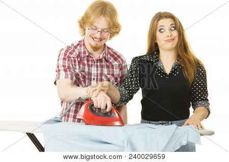 Woman trying to teach her stupid man how to do ironing clothes. Husband being silly. stock photo