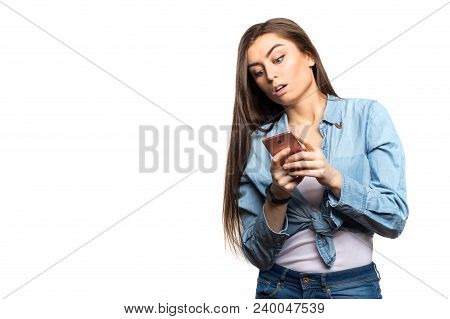 Portrait of a young brunette woman looking at the smartphone in her hands surprised against white background, isolated. Lifestyle, people and technology concept stock photo