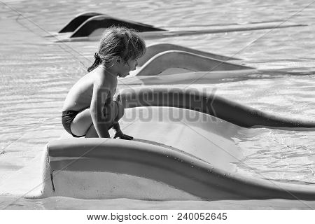 Happy cute baby boy with blond hair plays on yellow waterslide in outdoor pool on sunny summer day on water background stock photo