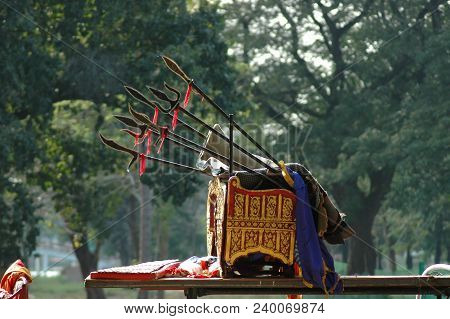 A chair used for royal ceremonies in Thailand. It is bright gold and red, with spears resting on top of it. Trees are in the background. stock photo