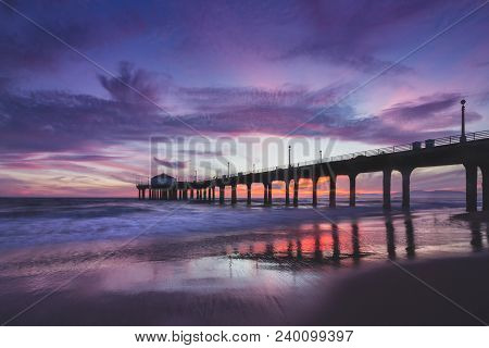 Long-exposure shot of colorful sky and clouds over Manhattan Beach Pier at sunset with smooth waves washing onto the beach, Manhattan Beach, California stock photo