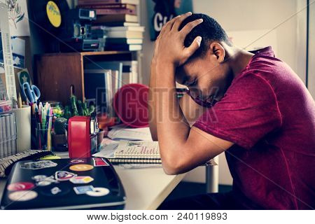 Teenage boy in a bedroom doing work stressed out and frustrated stock photo