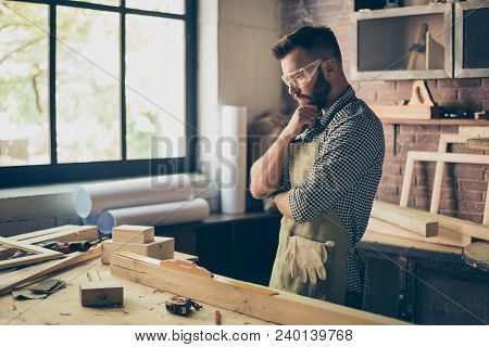 Pensive hardworking thoughtful serious concentrated minded cabinet-maker standing near table with instruments and thinking over new diy stock photo