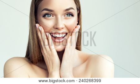 Happy beautiful girl holding her cheeks with a laugh   looking to the side. Expressive facial expressions  .Cosmetology and Spa , skin care model stock photo