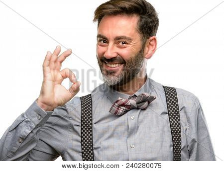 Middle age man, with beard and bow tie doing ok sign with hand, approve gesture isolated over white background stock photo
