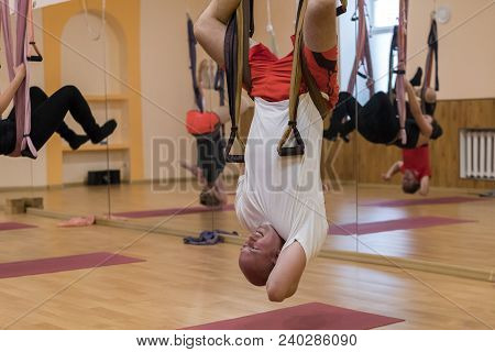 Anti-gravity Yoga, man doing yoga exercises. the man is hanging upside down. man warming up for training yoga by using hammocks for Anti-gravity air flying yoga. Wellness for lifestyle stock photo