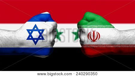 Flags of Israel and Iran painted on two clenched fists facing each other with flag of Syria in the background/Israel - Iran conflict concept stock photo