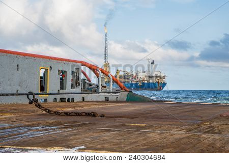 Anchor-handling Tug Supply AHTS vessel during dynamic positioning DPoperations near FPSO tanker. Vessel is doing static tow tanker lifting. Ocean tug job. stock photo