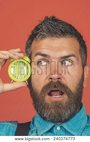 Surprised excited bearded man hold alarm clock near face. Bearded man with alarm clock on red background. Attractive macho with beard and mustache holding alarm clock near face. Time concept. stock photo
