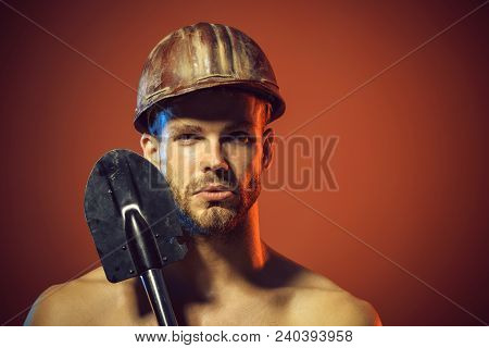 Army man holds shovel. Military, camping shovel. Male construction worker in hart hat holds spade. Muscle sexy professional builder, engineer, repairman in protective helmet with spade. Copy space. stock photo