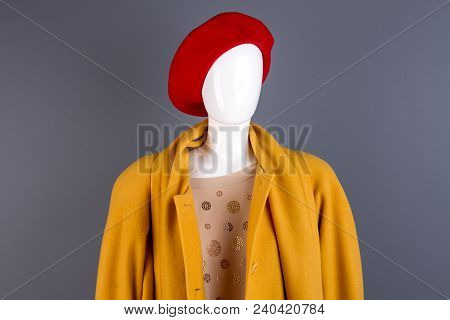 Portrait of mannequin in autumn outfit. Yellow stylish topcoat on mannequin, grey background. Couture outerwear on sale. stock photo