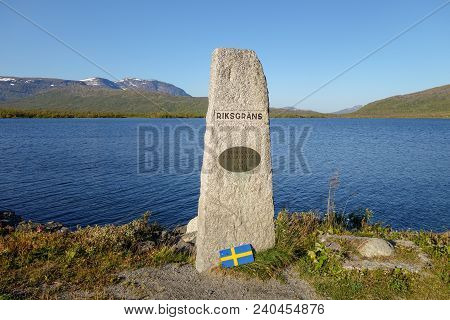 Summer day. Stone marking the border crossing between Sweden and Norway at E12 road to Mo I Rana. Road was made 1939. Umbukta lake in the back. stock photo