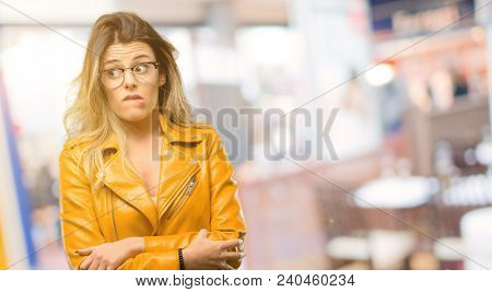 Beautiful young woman nervous and scared biting lips looking camera with impatient expression, pensive at restaurant stock photo