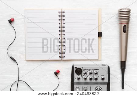 Audio recording studio desk table. Karaoke mock up. Song lyrics. Microphone, audio sound mixer, blank page notepad and headphones on white table background with copy space. stock photo